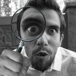 person looking through magnifying glass